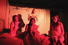 A photograph of a kneeling woman surrounded by three other women in white cloaks staring at her all in front of a painted backdrop