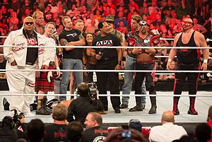 WWE Raw 1000 - WWE's returning legends standing over Heath Slater during Raw 1000.