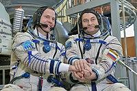 Soyuz MS-08 backup crew in front of the Soyuz spacecraft mockup.jpg