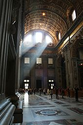 The main doors with light streaming in can be seen at the end of the nave. The enormous space dwarfs the people who are walking across the shining tiled floor.