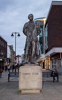 estátua ao ar livre de um homem em traje de passeio e vestido acadêmico