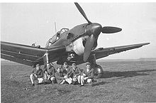 a single-engine monoplane parked on grass with men in uniform seated under the fuselage