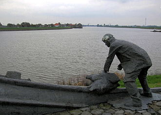 "North Sea flood of 1953 - Een dubbeltje op zijn kant"" (""A dubbeltje (small coin) on its edge"", meaning ""A narrow escape""), a sculpture by Roel Bendijk of de Twee Gebroeders in the Groenedijk"