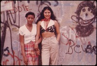TWO LATIN GIRLS POSE IN FRONT OF A WALL OF GRAFFITI IN LYNCH PARK IN BROOKLYN, NEW YORK CITY. THIS PROJECT IS A... - NARA - 555896.tif