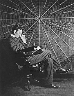 Tesla sitting in front of a spiral coil used in his wireless power experiments at his East Houston St. laboratory Teslathinker.jpg