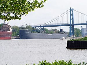 Gray barge sailing under a bridge