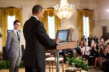 Man van in de twintig lachend naar links, man van in de veertig met computer in het midden, grote kristallen kroonluchter, meerdere mensen in het publiek