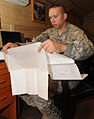 U.S. Army Sgt. 1st Class Wayne Hintz, a medic assigned to the 196th Maneuver Enhancement Brigade, South Dakota Army National Guard, studies the sexual assault evidence collection kit at Camp Phoenix 100815-A-GY802-009.jpg