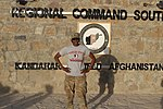 U.S. Army Spc. T'Ola Winston, an orderly room clerk with Charlie Company, Headquarters and Headquarters Battalion, 4th Infantry Division, poses with a Florida State football T-shirt at Kandahar Airfield 131004-Z-MH103-002.jpg