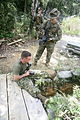 U.S. Marine Corps Sgt. Leon Branchaud, left, and Lance Cpl. Kowshon Ye, III Marine Expeditionary Force, Combat Camera, check their imagery before the next team reaches the pit and pond obstacle at Camp 090821-M-JL652-076.jpg