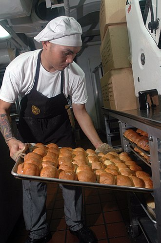 Baker - A U.S. Navy baker aboard the USS ''John C. Stennis'' aircraft carrier moves a tray of hot, freshly baked rolls onto a cooling rack.