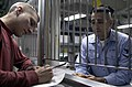 US Navy 030327-N-9403F-012 Disbursing Clerk 3rd Class Carlos Nolasco from San Antonio, Texas, helps a shipmate with a Split Pay form at the Disbursing Office service window aboard USS Abraham Lincoln (CVN 72).jpg