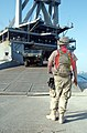 US Navy 040228-N-0743B-053 A U.S. Marine waits for a M-977 Heavy Expanded Mobility Tactical Truck (HEMTT) to roll off the ramp of the Military Sealift Command (MSC) fast sealift ship USNS Bellatrix (T-AKR 288).jpg