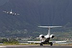 US Navy 040421-N-3228G-008 A C-20G Gulfstream aircraft taxis to the runway for a local training flight while a P-3C Orion prepares to land.jpg