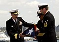 US Navy 050321-N-8213G-064 Commander, Carrier Strike Group Fifteen (CSG-15), Rear Adm. Robert J. Cox, left, receives his personal flag during the disestablishment ceremony for CSG-15 aboard the Nimitz-class aircraft carrier USS.jpg