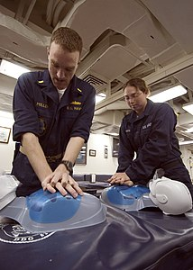US Navy 070515-N-5253W-001 Ensign Michael Miller (left) and Seaman Deana Hakes assigned to the Arleigh Burke-class guided-missile destroyer USS Lassen (DDG 82) practice chest compressions on mannequins during cardio-pulmonary r.jpg