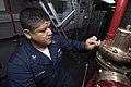 US Navy 070717-N-5387K-007 Aviation Boatswain's Mate (Fuel) 2nd Class Jose Requena polishes an installed fire fighting system while cleaning aboard USS Kitty Hawk (CV 63).jpg