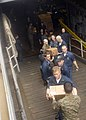 US Navy 100119-N-2000D-031 Sailors and Marines aboard the amphibious dock landing ship USS Carter Hall (LSD 50) load meals-ready-to-eat (MREs) onto pallets for delivery to earthquake victims.jpg