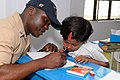 US Navy 100315-N-8335D-125 Logistics Specialist 1st Class Patrick Lampley draws a picture during a community service project at Shishu Niketm-1 elementary school.jpg