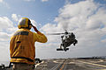 US Navy 110412-N-SG869-110 Personnel Specialist 2nd Class Edwin Barrientos signals for an SH-60B Sea Hawk helicopter to land aboard the guided-miss.jpg