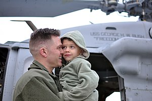 US Navy 111210-N-FU443-312 A Sailor hugs his son during the squadron's homecoming ceremony.jpg