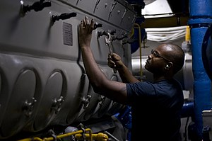 US Navy 120110-N-TZ605-202 ngineman 3rd Class Mark Jones performs maintenance on an engine valve in an emergency diesel generator space.jpg
