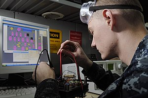 US Navy 120215-N-RG587-184 Electronics Technician 3rd Class Chris Elmendorf tests the connectivity of a circuit board in the micro-miniature repair.jpg