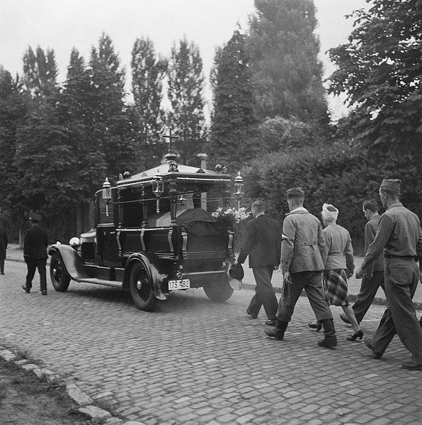 File:Uitvaart lijkwagen wordt gevolgd door geuniformeerde mannen en een vrouw, Bestanddeelnr 900-3468.jpg