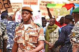 Military of Mali - A national guard soldier walks by demonstrators at Bamako airport.