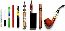 Displaying a variety of e-cigarettes standing next to each other. It includes an e-cigarette designed to look like a tobacco cigarette, an e-cigar, and an e-pipe.