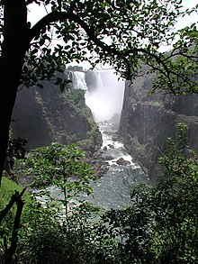 A majestic African scene. The viewer stands beneath a tree, overlooking the a large river from a high vantage point on a pleasant, sunny day. On each side of the river a great cliff rises above the viewer. In the distance an enormous waterfall can be seen, the spray from the water obscuring much of the view. The land is green and lush, and the river shimmers in the sun.