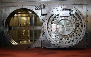 Bank vault - This large 24-bolt Diebold vault door at the Winona National Bank was built in the early 1900s. On the right is the back side of the open door. To the right of the door's center are two linked boxes for the combination mechanisms and to the left is a four movement time lock.  This door has a four-point pressure system (note the two pressure system stanchions left of the door opening) capable of exerting 1/3 of the door's weight in pressure. Since this door weighs 22.5 tons (45,000 Lbs.) its pressure system is capable of applying 7.5 tons (15,000 Lbs.) of pressure.