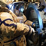 Working on the airlock hatch in the Orlan (8101838724).jpg