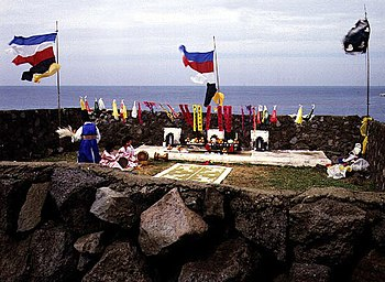 An outdoor shaman ritual, with several flags and banners.