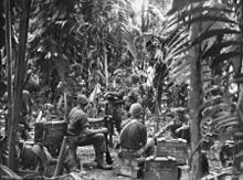 Soldiers sitting on stores boxes at a military camp surrounded by thick jungle