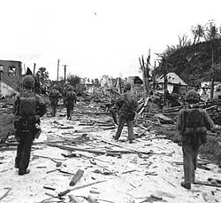 A group of Marines in a tactical column patrolling down a street through the ruins of a devastated town.
