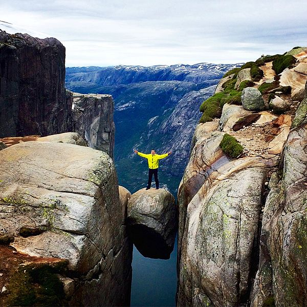 A man standing on Kjeragbolten in Norway. Photo by Scoundrelgeo.