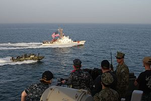 A riverine command boat speeds alongside the U.S. Coast Guard Cutter Adak.jpg