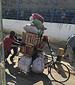 African man carrying baggage on bicycle.jpg