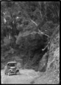 An unidentified man standing beside a car on the Akatarawa Road, 1923 ATLIB 299517.png