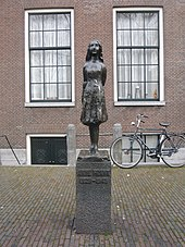 "A bronze statue of a smiling Anne Frank, wearing a short dress and standing with her arms behind her back, sits upon a stone plinth with a plaquereading ""Anne Frank 1929–1945"". The statue is in a small square, and behind it is a brick building with two large windows, and a bicycle. The statue stands between the two windows."