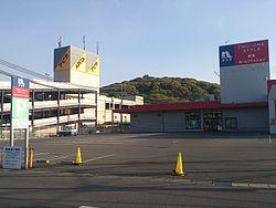 店舗の東側に隣接するナフコツーワンスタイル小牧店(現在は閉店)。中央(小牧山)の山頂に見えるのは小牧城(小牧市歴史館)