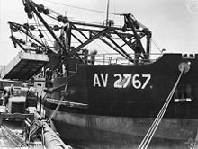 Black and white photo of a ship docked at a wharf. The ship's cranes are lifting a container above a truck.