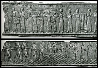 Balawat - The Walters Art Museum fragments of the Balawat Gates. (Top) Syrian porters in long robes and conical hats carry tribute to the Assyrian camp. (Bottom) Assyrian soldiers carry logs as they march through a hilly, forested landscape