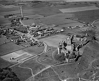 Bamburgh Castle - An aerial photograph from 1973 showing the position of the castle north east of Bamburgh village