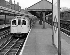 A westbound Piccadilly line train at Barons Court station, operated by a seven-car 1959 stock.