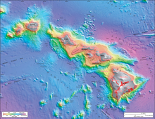 Bathymetric rendering of the Hawaiian island chain showing greater depths as blue, shallower depths as red, and exposed land as gray. The main island is the tallest, the ones in the middle sit on a raised plateau, and three more islands sit separately at the west end of the chain. A series of small elevation bumps (seamounts) sit south of the main landmass.