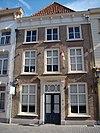 foto van Huis met eenvoudige gecemente lijstgevel en empire consoles onder de kroonlijst