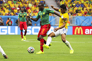 Paulinho (footballer) - Paulinho battles Cameroon midfielder Landry N'Guémo for the ball during the 2014 FIFA World Cup on June 23.
