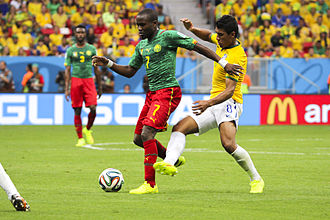 Nicolas Nkoulou - Nkoulou observes on the background as his compatriot Landry N'Guémo battles Brazil midfielder Paulinho for the ball during the 2014 FIFA World Cup in June 23.